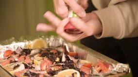 Närbilden av händer av en flicka på det hem- köket är salta, eller peppra en maträtt i en prodvin av en handbok mala Sunt arkivfilmer