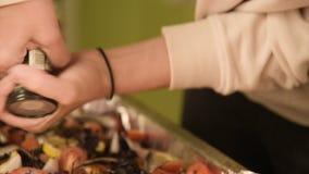 Närbilden av händer av en flicka på det hem- köket är salta, eller peppra en maträtt i en prodvin av en handbok mala Sunt stock video