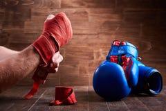 Närbilden av händerna av en ung boxare, som spolar boxning, förbinder och handskar Arkivfoto