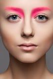 Närbilden av härligt modellerar vänder mot med danar det rosa sminket, rengöring flår Royaltyfri Fotografi