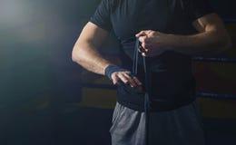 Närbilden av handen av en ung boxare, som spolar boxning, förbinder Arkivfoto