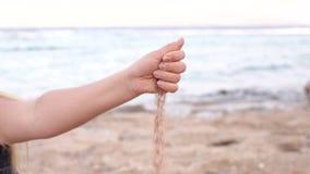Närbilden av handen för flicka` s häller sand på stranden lager videofilmer