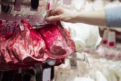 Närbilden av handen av flickan i en underkläder shoppar väljer en behå Sexig underkläder i en moderiktig boutique Shopping av und arkivbild