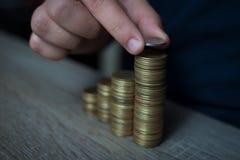 Närbilden av handen satte mynt till bunten av mynt, sparande pengar för begrepp Royaltyfri Fotografi