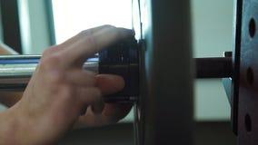 Närbilden av handknipor låser för diskett på skivstången för powerlifting arkivfilmer