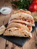Närbilden av hemlagade tortillor med kryddig höna, grönsaker och salsa doppar på trätabellen royaltyfri fotografi
