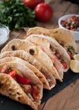 Närbilden av hemlagade tortillor med kryddig höna, grönsaker och salsa doppar på trätabellen arkivfoto