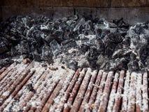 Närbilden av kol klumpa sig och metallkuggen som täckas med askaen arkivbilder