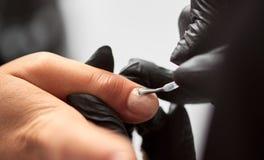 Närbilden av kosmetologhänder som att applicera som är genomskinligt, stelnar, polerar på kvinnafingernaglar i skönhetsalong royaltyfri fotografi