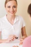 Närbilden av kosmetologhandmålning spikar av kvinna i salong Arkivfoto