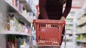 Närbilden av kvinnahanden sätter produkter in i vagnen nära hyllor i supermarket stock video
