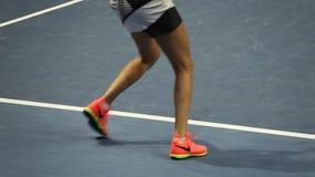 Närbilden av kvinnlign lägger benen på ryggen i rörelse på tennisbanan arkivfilmer