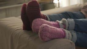 Närbilden av kvinnlign lägger benen på ryggen i woolen sockor, hemtrevlighet, omsorg, vänlighet, värme, fps för affektion 60 arkivfilmer