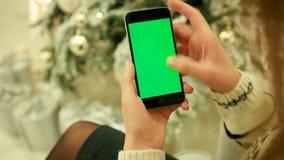 Närbilden av kvinnlign räcker den rörande gröna skärmen på mobiltelefonen Två i en: 1 close upp Spåring av rörelse vertikalt med lager videofilmer
