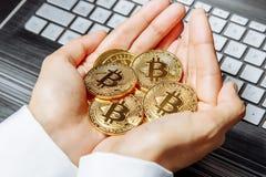 Närbilden av kvinnlign räcker hållande massor av bitcoins på bärbar datortangentbordbakgrund arkivfoton