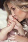 Närbilden av kyssande baby'sens för den lyckliga modern fot hennes nyfött behandla som ett barn gi Royaltyfri Fotografi