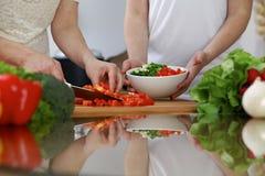 Närbilden av människan räcker matlagning i ett kök Vänner som har gyckel, medan förbereda ny sallad Vegetarian som är sund mig royaltyfria foton