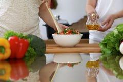 Närbilden av människan räcker matlagning i ett kök Vänner som har gyckel, medan förbereda ny sallad Vegetarian som är sund mig royaltyfria bilder