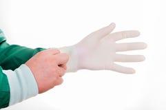Närbilden av manlig doktors` s räcker att sätta på steriliserad kirurgisk handske arkivfoto