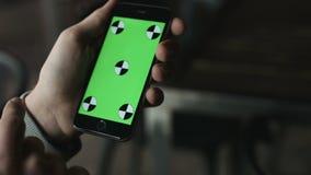 Närbilden av mannen räcker att trycka på av smartphonen Grön skärmChromatangent close upp Spåring av rörelse vertikalt flåsanden arkivfilmer