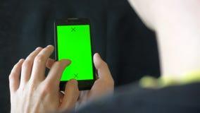 Närbilden av mannen räcker att trycka på av smartphonen Grön skärmChromatangent close upp Spåring av rörelse vertikalt flåsanden  stock video