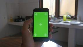 Närbilden av mannen räcker att trycka på av smartphonen i köket Grön skärmChromatangent lager videofilmer