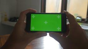 Närbilden av mannen räcker att trycka på av smartphonen i köket Grön skärmChromatangent stock video