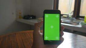 Närbilden av mannen räcker att trycka på av smartphonen i köket Grön skärmChromatangent arkivfilmer
