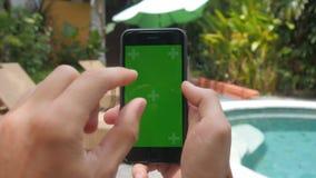 Närbilden av mannen räcker att trycka på av smartphonen på semestern på pölbakgrund Grön skärmChromatangent arkivfilmer