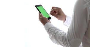 Närbilden av mannen räcker genom att använda smartphonen nära fönstret lager videofilmer