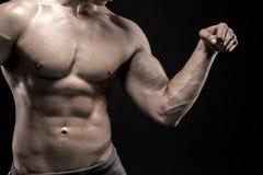 Närbilden av mannen som böjer som visar hans triceps, biceps tränga sig in royaltyfri bild
