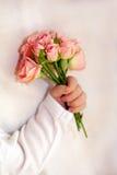 Närbilden av nyfött behandla som ett barn handen med blommor Arkivfoto
