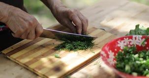 Närbilden av rynkiga händer för farmor` s klippte dillen på ett träbräde utomhus lager videofilmer