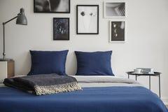 Närbilden av säng med blått sängkläder och mörker färgade filten Nattduksbord med böcker och kaffe bredvid det royaltyfri bild