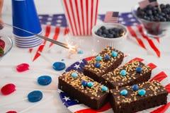 Närbilden av söt mat och brinnande smällare dekorerade med 4th det juli temat Royaltyfri Foto
