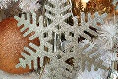 Närbilden av silver blänker snöflingan formade julprydnaden med den guld- formade prydnaden för gritteren bollen Royaltyfria Foton