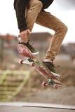 Närbilden av skateboardersfoten, medan åka skridskor i skridsko, parkerar royaltyfri foto