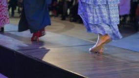 Närbilden av skor på podiet, den härliga kvinnlign lägger benen på ryggen, samlingsskor, modeller i höga häl på catwalk i klännin stock video