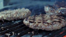 Närbilden av tre hamburgarekotletter som grillas, rök kommer från varma kol royaltyfri foto