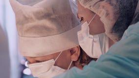 Närbilden av två kirurger vänder mot i maskeringar som diskuterar detaljerna av operationen lager videofilmer