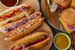 Närbilden av varmkorvar och hamburgare dekorerade med 4th det juli temat Arkivbild