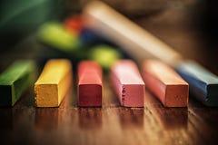 Färgrika kritapinnar på trä ytbehandlar Royaltyfri Bild