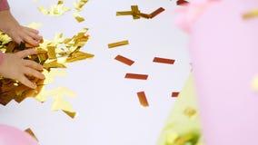 Närbilden barns händer spelar med guld blänker, guld- paljetter från smällare, festligt glitter, garneringar arkivfilmer