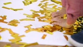 Närbilden barns händer spelar med guld blänker, guld- paljetter från smällare, festligt glitter, garneringar lager videofilmer