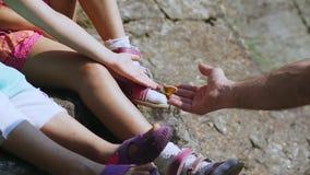 Närbilden en härlig orange bergfjäril sitter på en fot för barn` s i sandaler den manliga handen försöker att ta, fångar a stock video