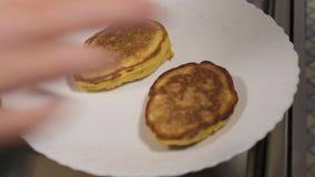 Närbilden en kvinna sätter en panna på en platta av pannkakor arkivfilmer