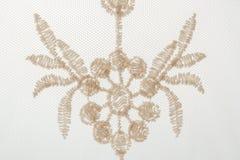 Närbilden ett fragment av snör åt med utsmyckat blom- motiv på vit b arkivbild
