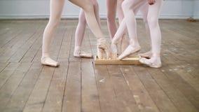 Närbilden foten av unga dansare, flickorna fäller ned spetsarna av pointeskorna in i en ask med specialt pulver arkivfilmer
