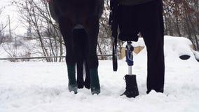 Närbilden hästben som spolas tillbaka med, förbinder och manliga ben av en rörelsehindrad ryttare mannen har en protes i stället  lager videofilmer