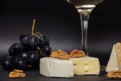 Närbilden högg av camembertost, muttrar och söta blåa druvor på bakgrunden av ett exponeringsglas av vitt torrt vin royaltyfri bild